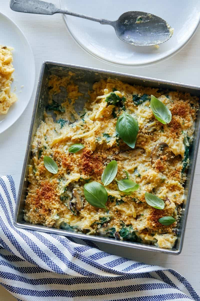 A pan of creamy vegan spaghetti squash, wild mushroom, and spinach bake.