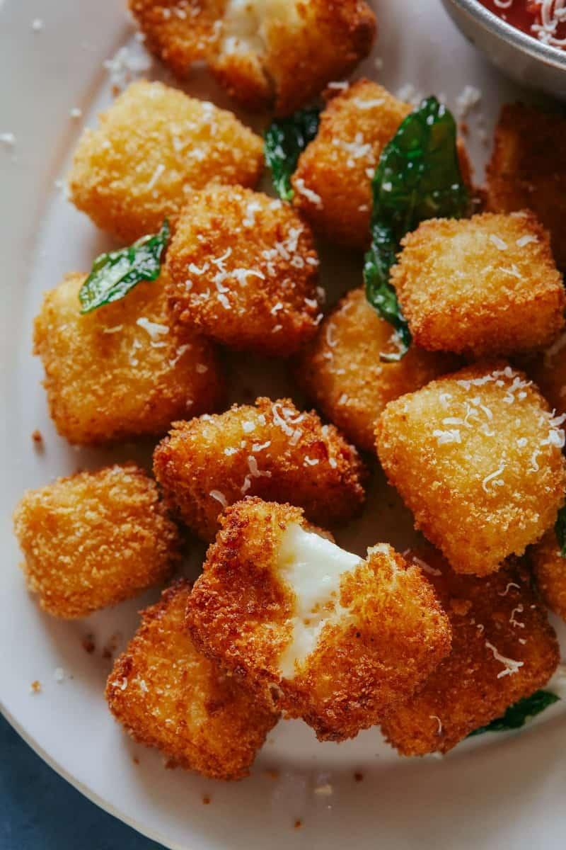 A close up of hallumi nuggets with marinara sauce.