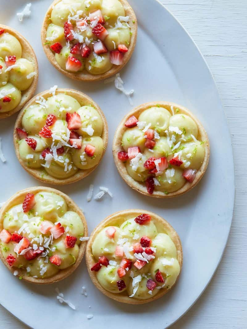 Several coconut lime tarts topped with sugar soaked strawberries.