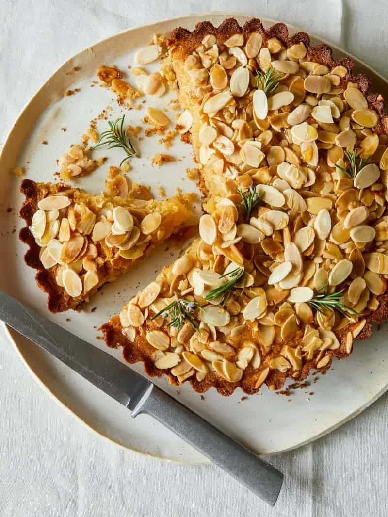 A sliced almond and honey cornmeal cake with a knife.