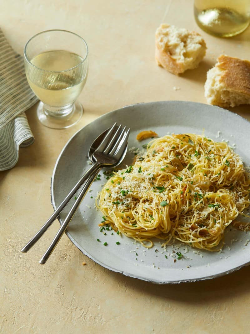 Garlic and herb capellini on a plate with a fork, spoon, bread, and a drink.