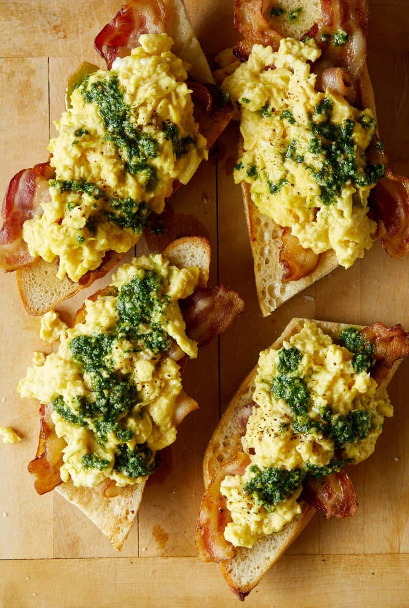 A close up of pesto topped scrambled eggs and bacon over toasted baguette.