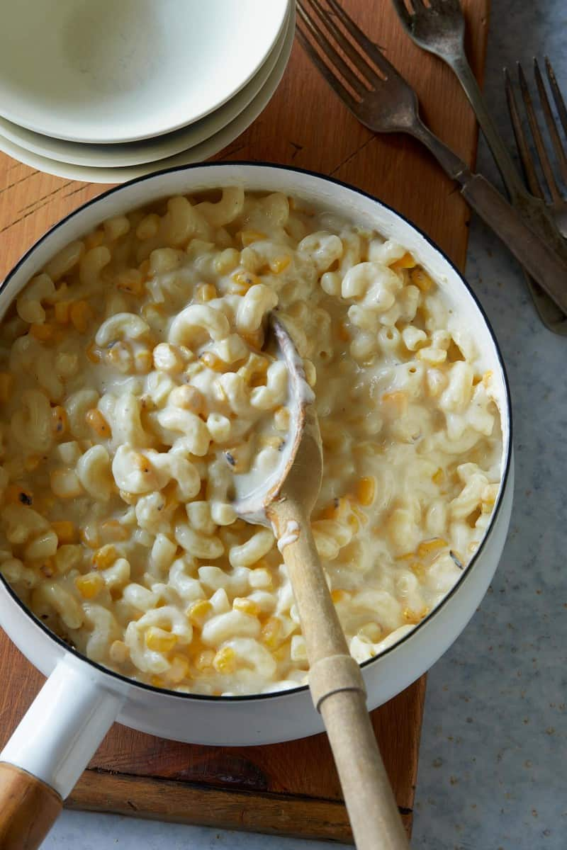 A pot of creamed corn mac and cheese with a wooden serving spoon.