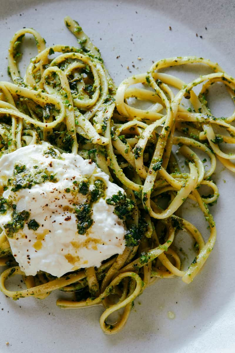 A close up of English pea, basil, and pistachio pesto linguine topped with burrata.