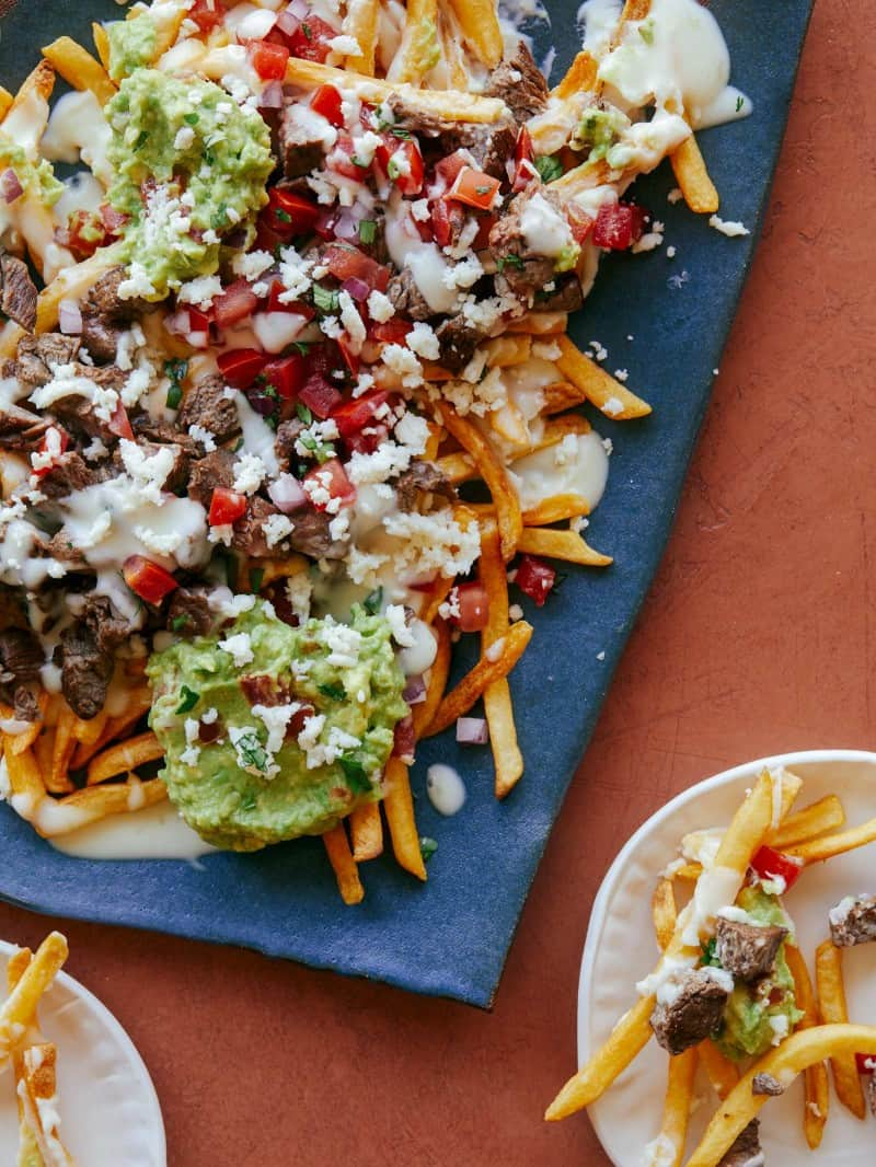 Carne asada fries on a blue platter with a serving on a small plate.
