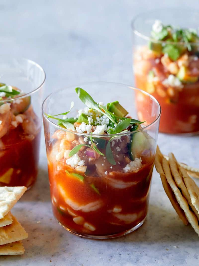 A close up of glasses of Mexican shrimp cocktails with saltine crackers.