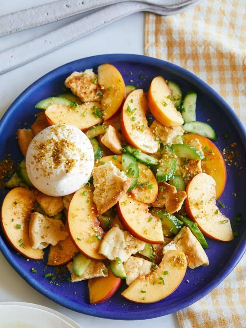 Peach panzanella salad on a blue plate.