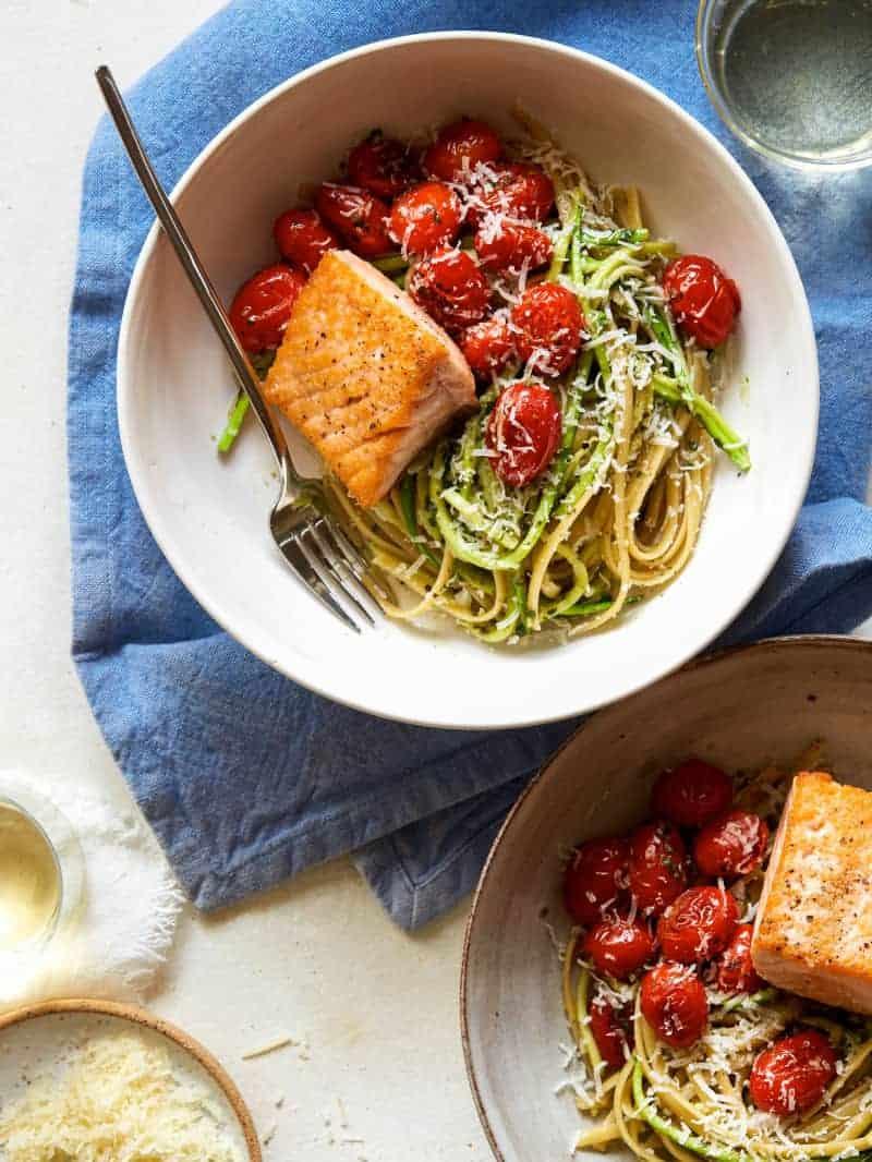 Seared salmon over 50/50 spaghetti with arugula and walnut pesto with a fork.
