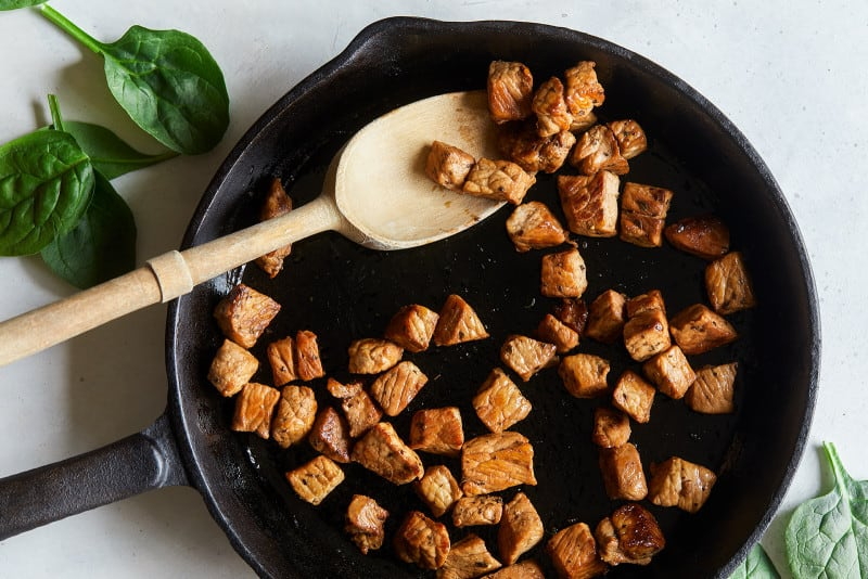 A pan filled with pieces of cooked pork loin with a wooden spoon.