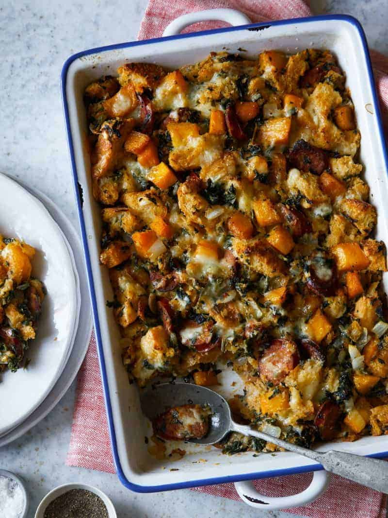 A baking dish of butternut squash sage stuffing with plates and a spoon.