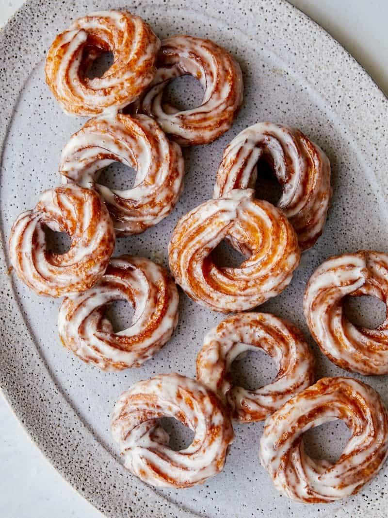 Pumpkin crullers with vanilla bean glaze on a platter.
