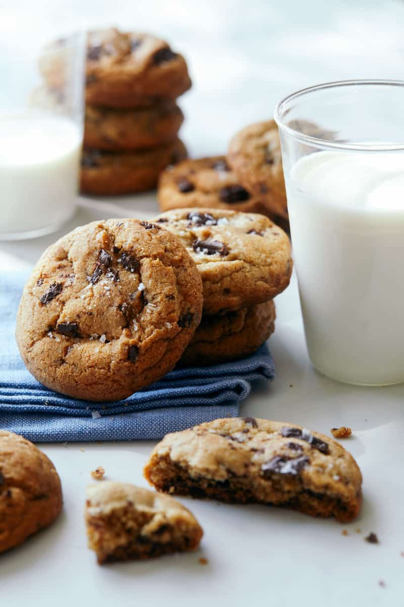A close up of stacked salted brown butter chocolate chips cookies and milk.