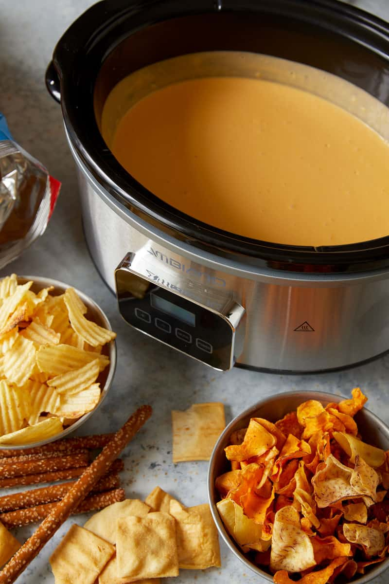 A crock pot of beer cheese with chips.