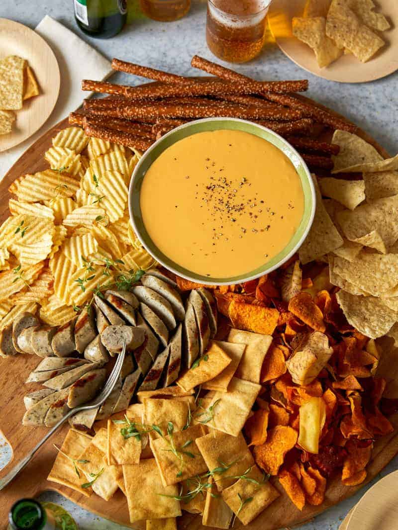 Crock pot beer cheese dip with chips and meat for dipping.