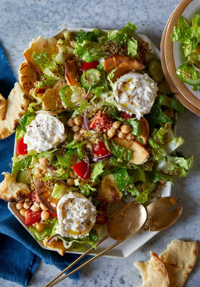 A close up of fattoush style salad with crispy quinoa on a platter.