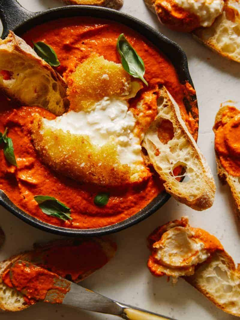 A close up of fried burrata over romesco sauce with bread.