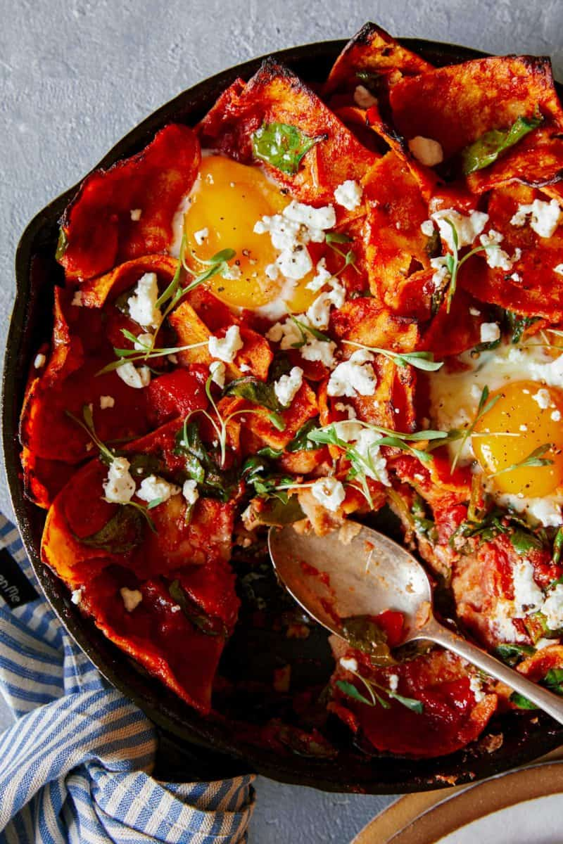 A close up of shakshuka chilaquiles in a pan with a spoon.