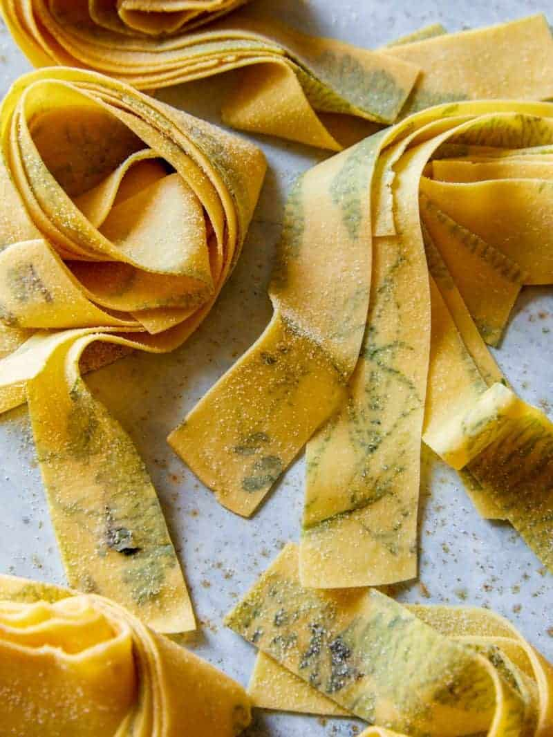 A close up of uncooked herb laced pappardelle.