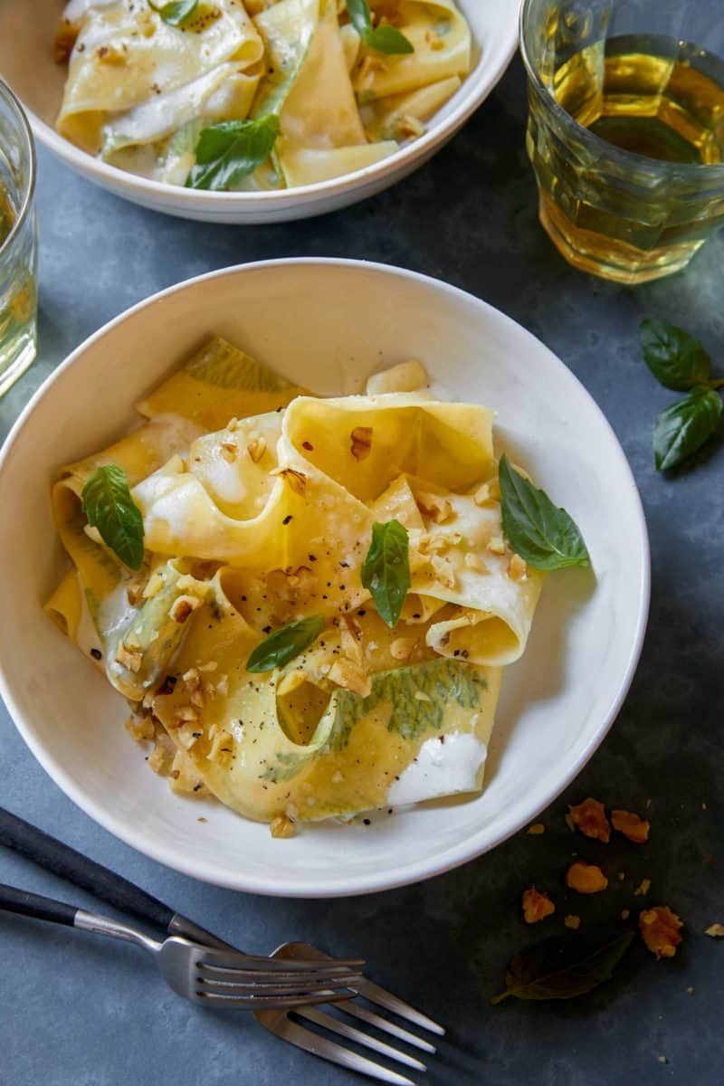 A bowl of herb laced pappardelle in walnut cream sauce.