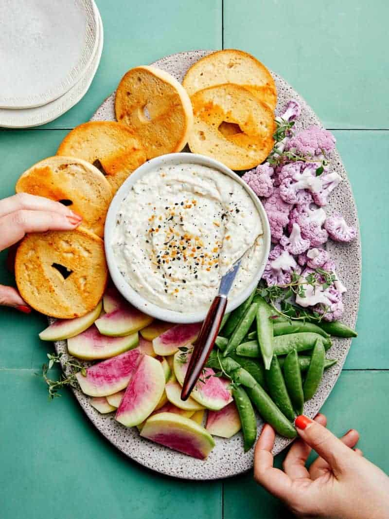 Everything seasoning and caramelized onion dip on a platter with bagels and veggies.
