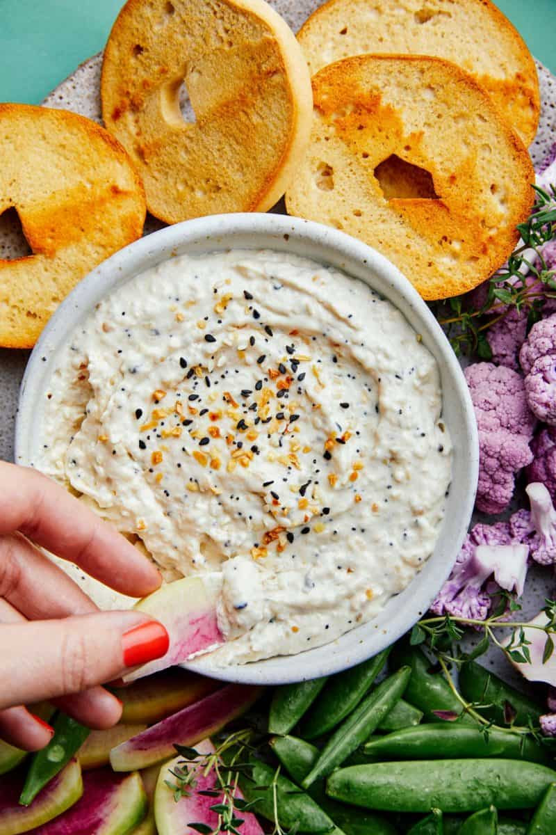 A close up of everything seasoning and caramelized onion dip with bagels.