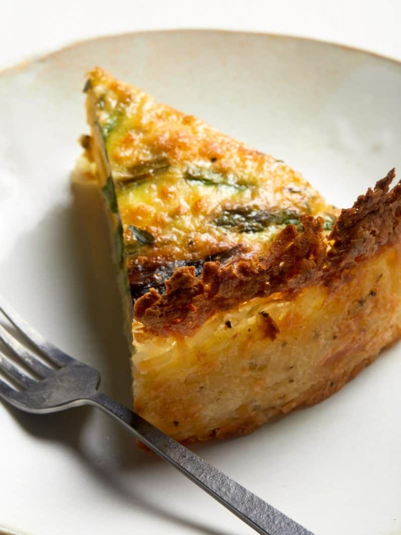A close up of a slice of spring quiche with hash brown crust with a fork.