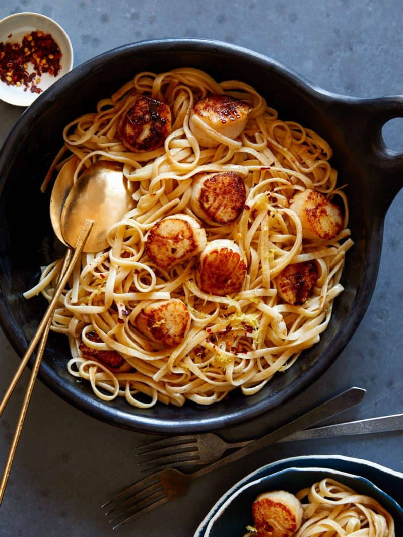 Linguine with brown butter sauce and scallops in a skillet with spoons.