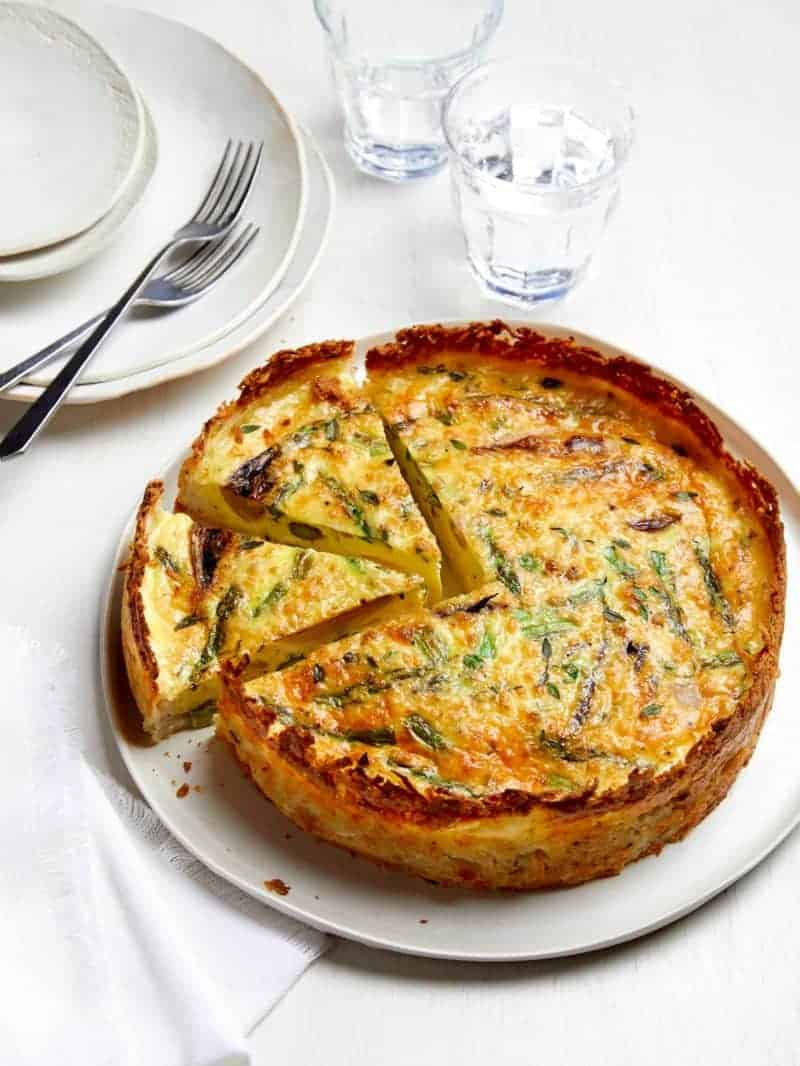 A whole sliced spring quiche with hash brown crust with extra plates and forks.
