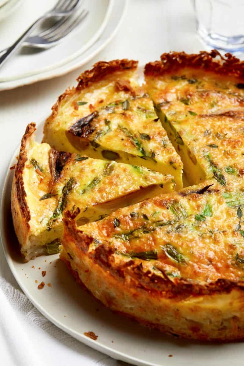 A close up of sliced spring quiche with hash brown crust.