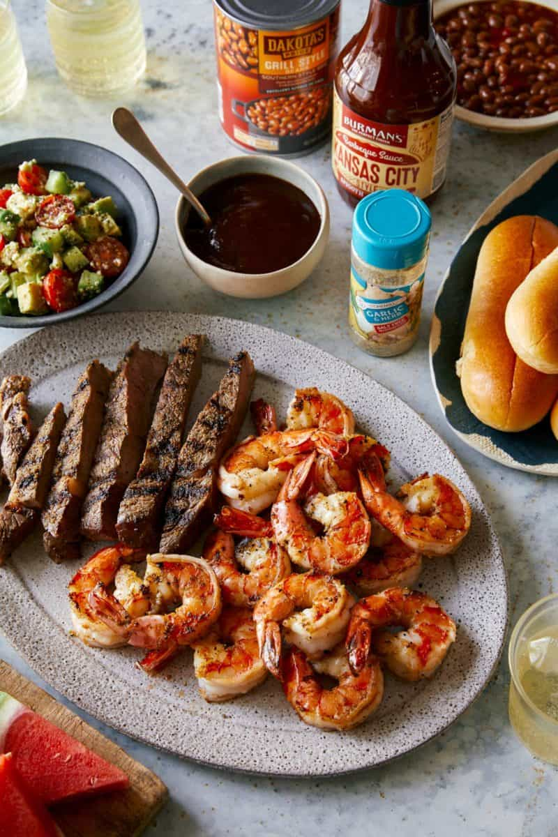 Grilled shrimp and steak platter with sides of salad, sauces and rolls.