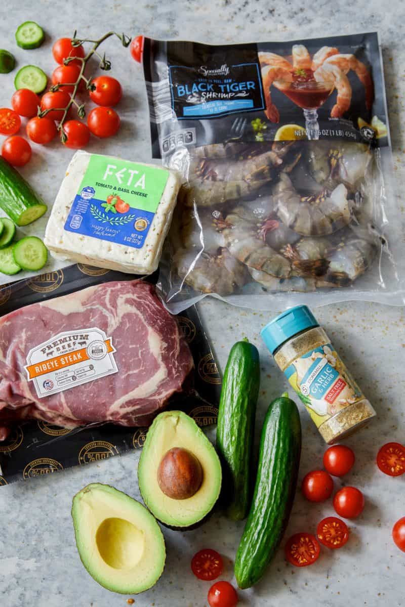 Packaged and raw ingredients for grilled shrimp and steak platter.