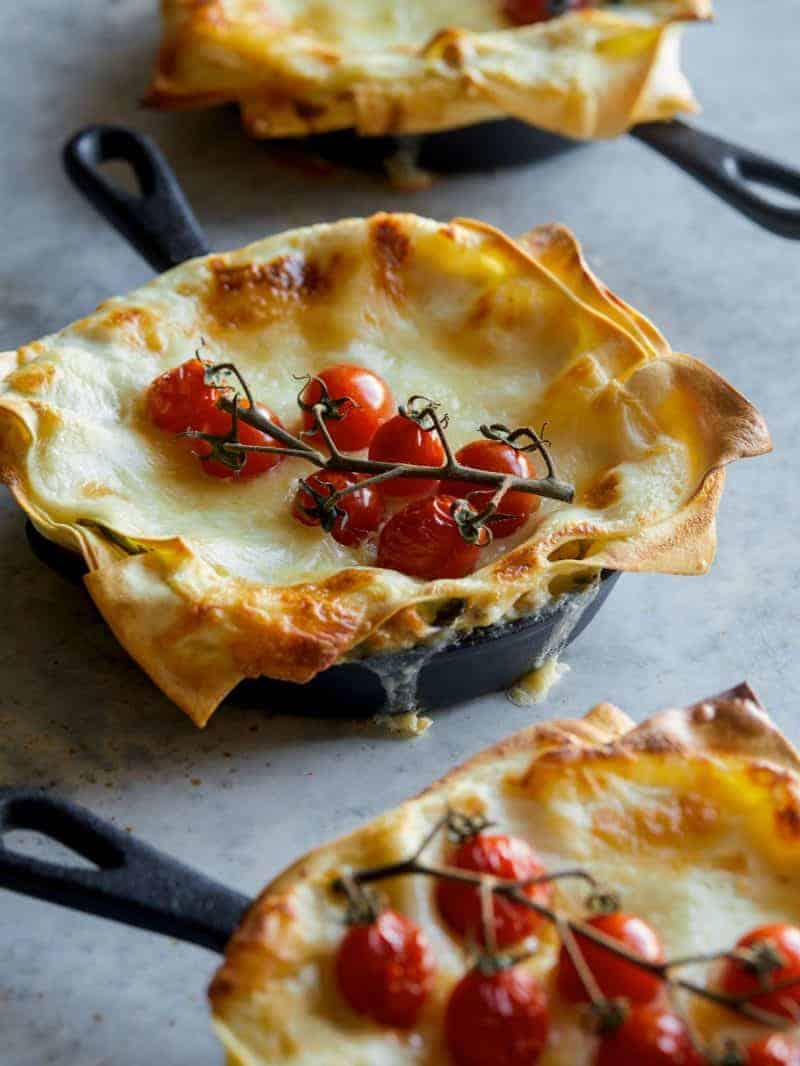 A close up of an creamy turkey kale skillet lasagne with a vine of cherry tomatoes.