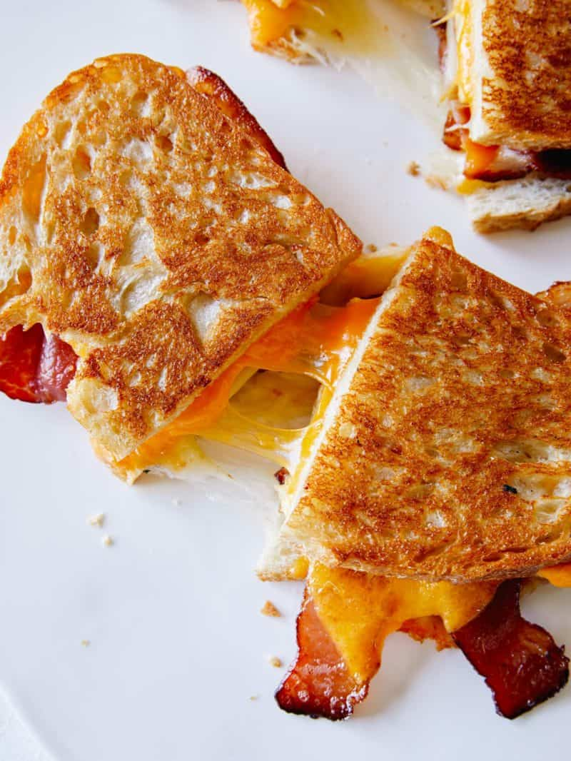 Extra cheesy breakfast grilled cheese sandwiches cut in half.