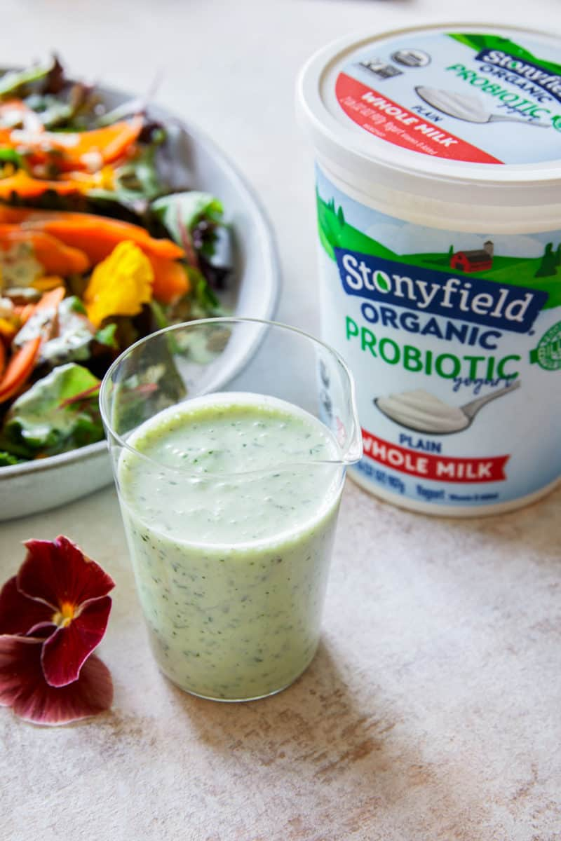 Green goddess dressing in a glass next to Stonyfield organic yogurt and a summer salad.