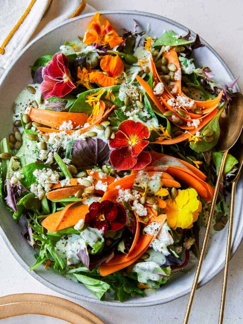 A summer salad with green goddess dressing and spoons.