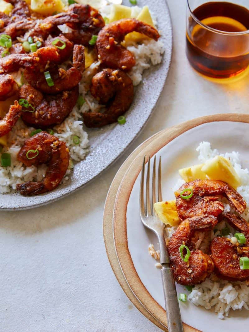 Hawaiian style crispy garlic butter shrimp over white rice, served with a fork.