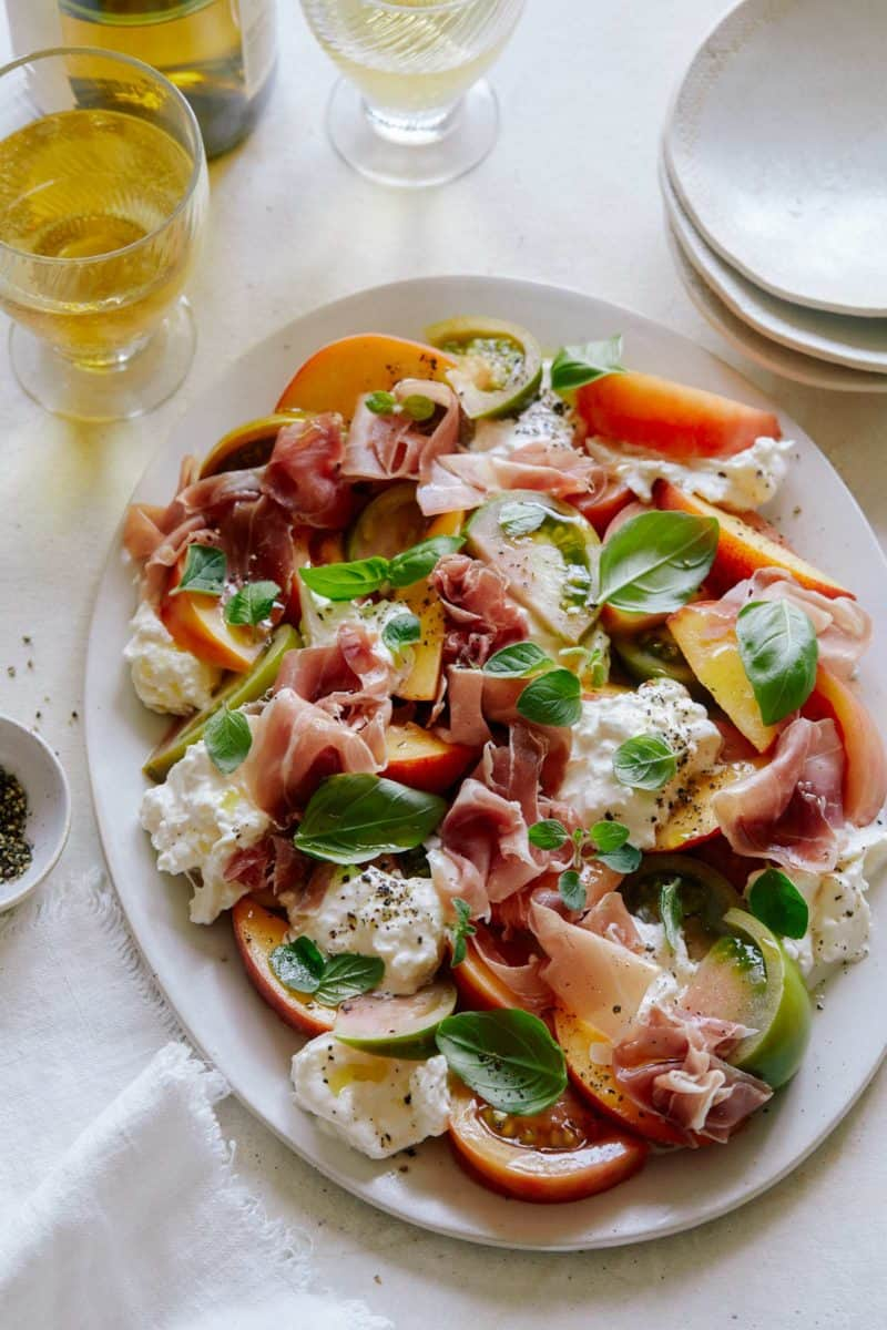 Heirloom tomato, peach, and burrata summer plate with plates.