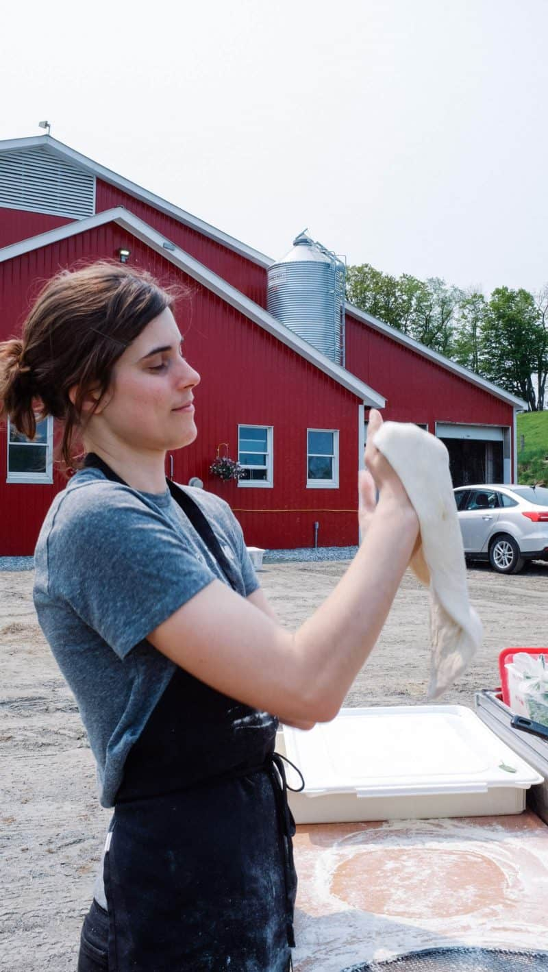 A woman holding pizza dough in front of a farm.