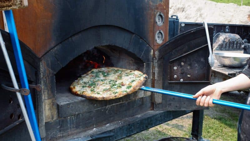A pizza being removed from a wood burning pizza oven.