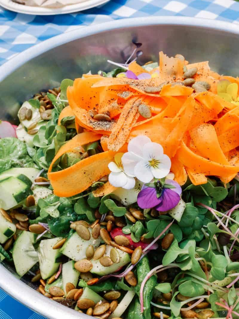 A close up of a summer salad with green goddess dressing.