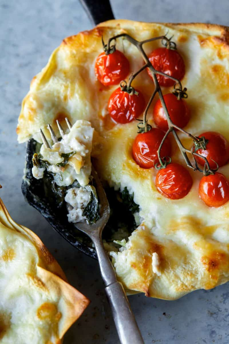A close up of individual creamy turkey and kale skillet lasagne with a fork.