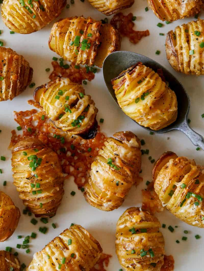 Mini cheesy hasselback potatoes with one on a spoon.