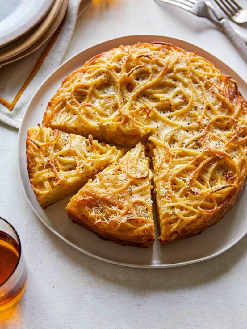 Cacio e pepe pasta pie with slices cut.