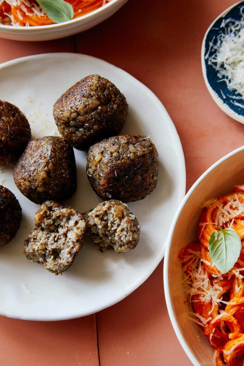 Vegan meatballs on a plate next to creamy roasted red pepper spaghetti.