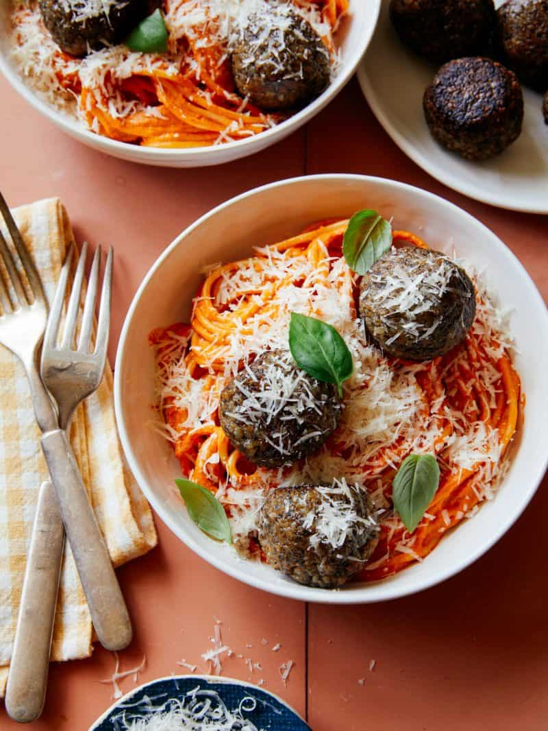 Vegan creamy roasted red pepper spaghetti and meatballs in a bowl with forks.