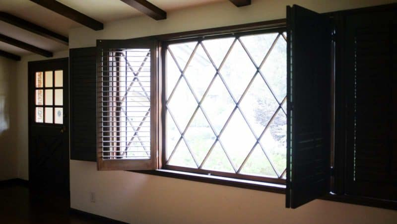 A room with a large window with open shutters.