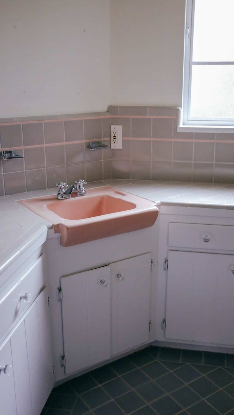 A bathroom counter and pink sink with a window