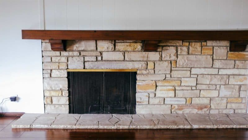 A stone fire place in a living room.