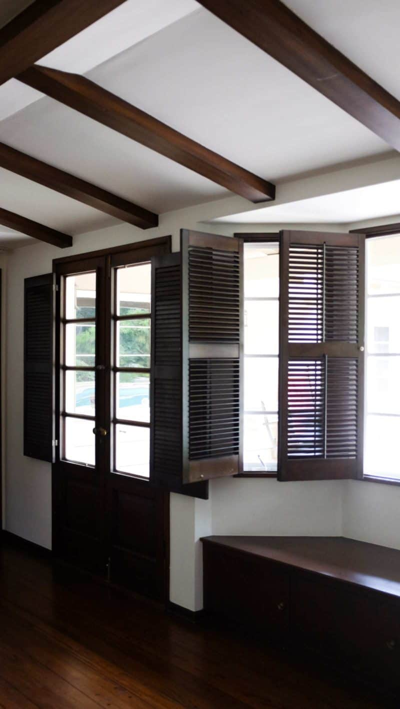 A room with large windows with open shutters and french doors.