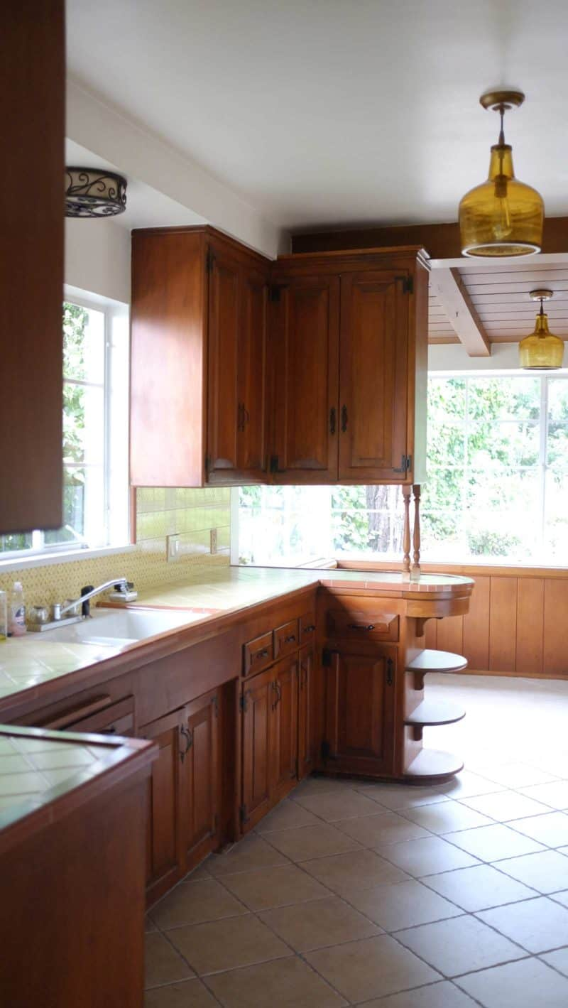 A kitchen with a sink and a window looking into eat in area.